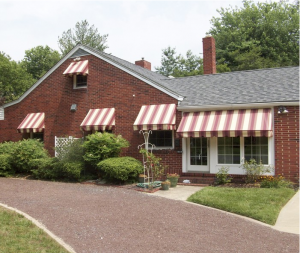 brick hosue with red & tan awnings