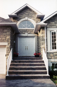 Cobblestone house with white railing and door